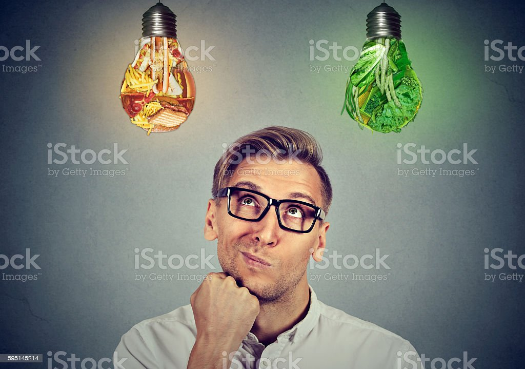 Man looking up at vegetables light bulb junk food stock photo