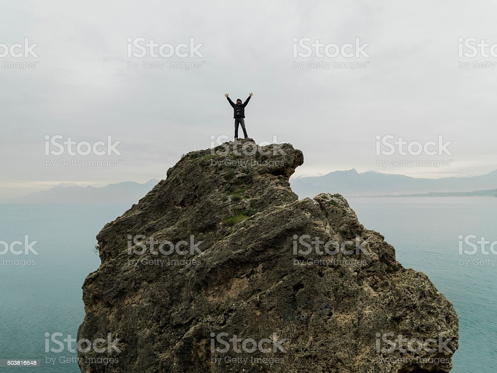 Man looking up on top of cliff stock photo