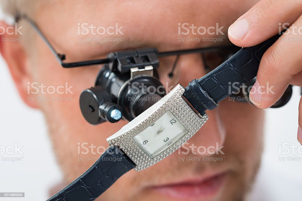 Man Looking Wrist Watch With Loupe stock photo