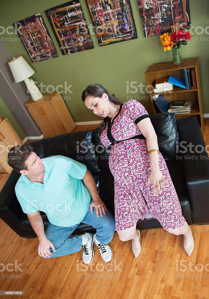 Man Looks at Clumsy Pregnant Woman stock photo