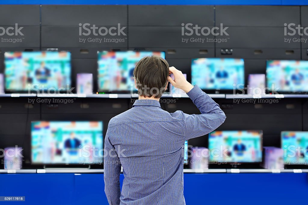 Man looks at LCD TVs in store stock photo