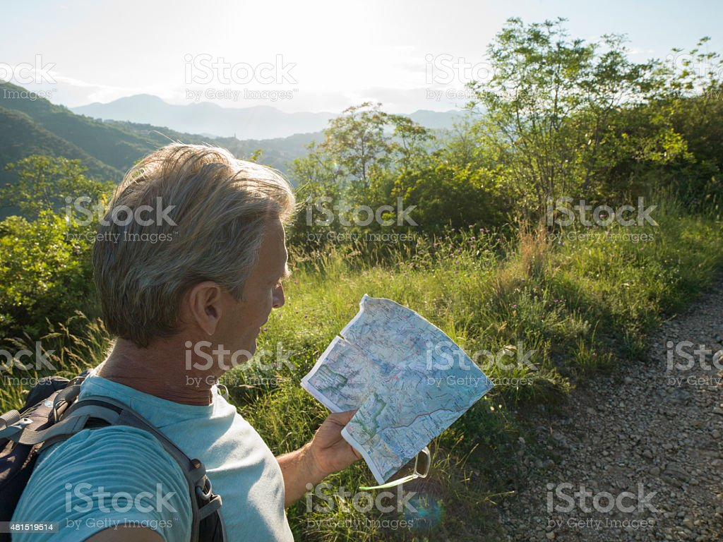 Man looks at map for guidance in Liguria, Italy. stock photo