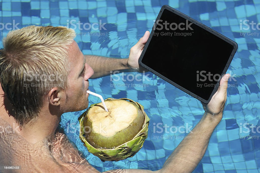 Man Looks at Tablet Computer Sipping Coconut in Pool stock photo