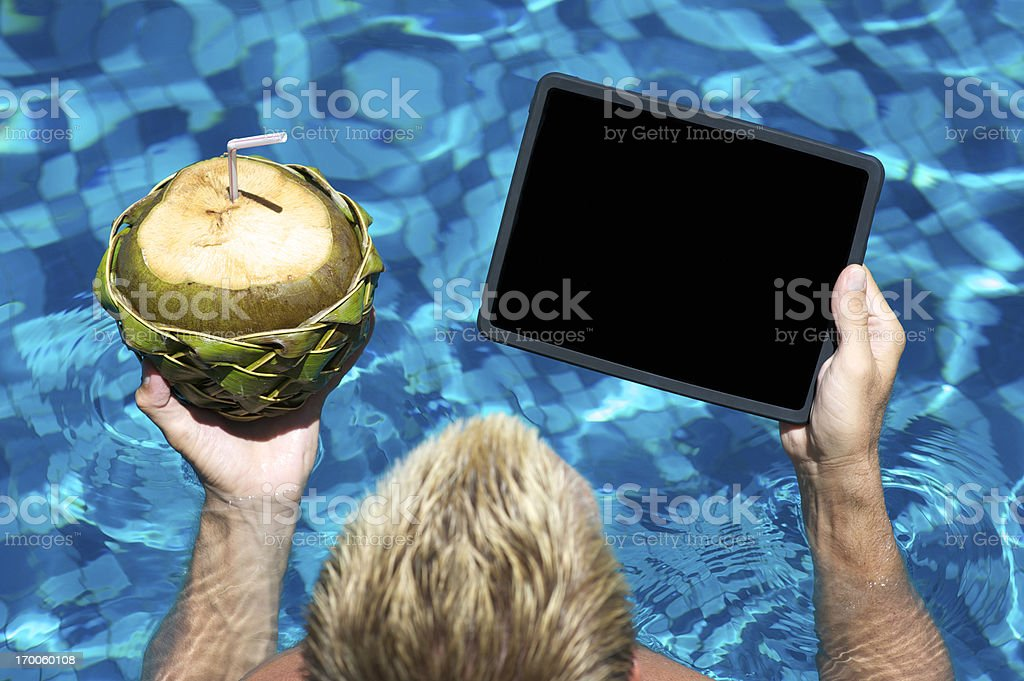 Man Looks at Tablet Computer with Fresh Coconut in Pool stock photo