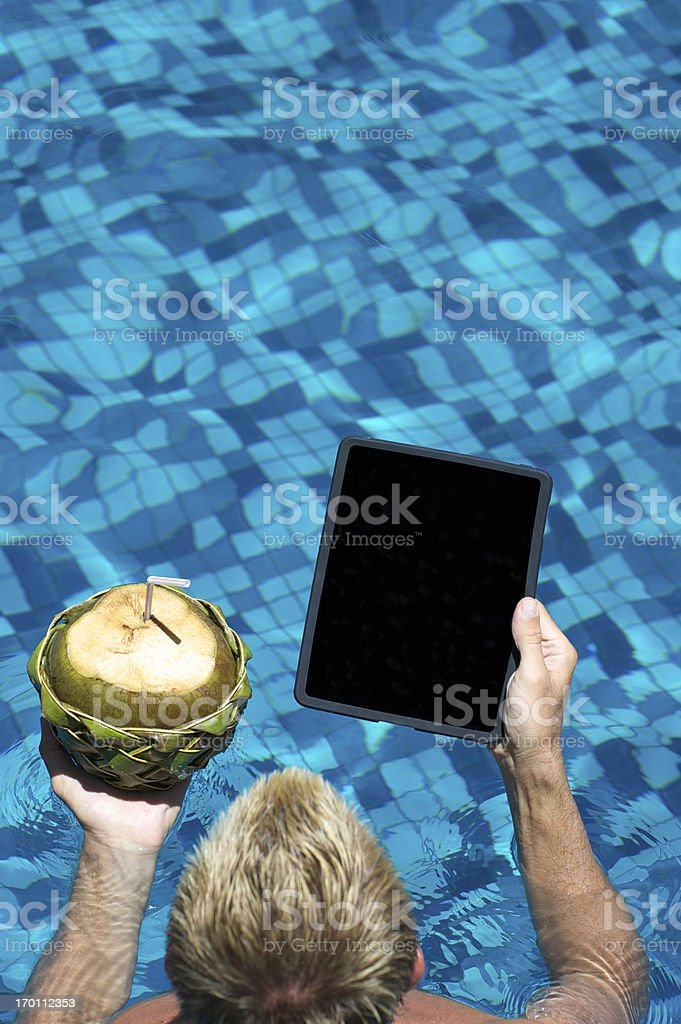 Man Looks at Tablet Computer with Fresh Coconut in Pool royalty-free stock photo