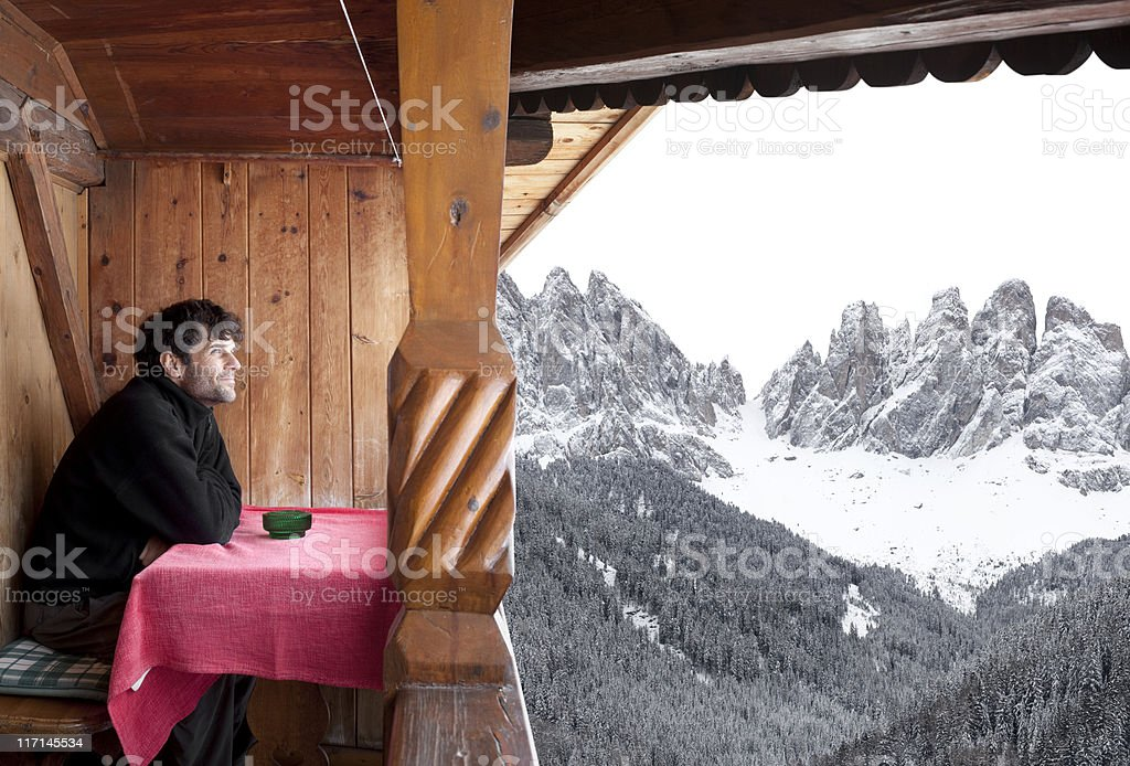 Man looks at the mountains from an alpine hut stock photo
