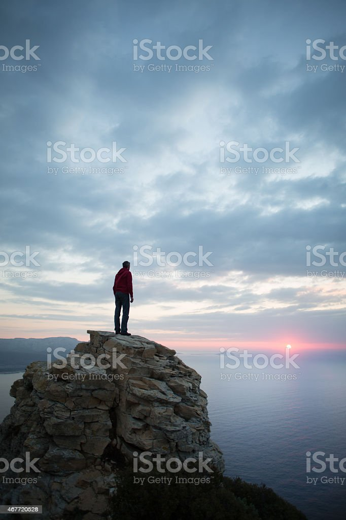 Man looks at the seascape from a cliff stock photo