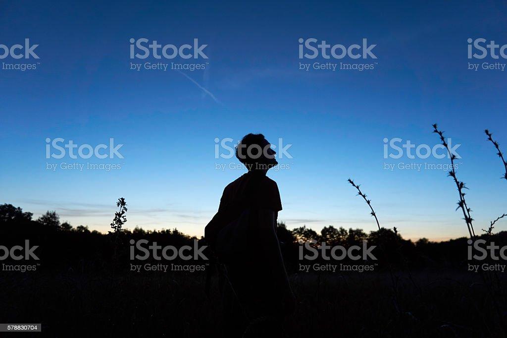 Man looks at the sky hopefully stock photo