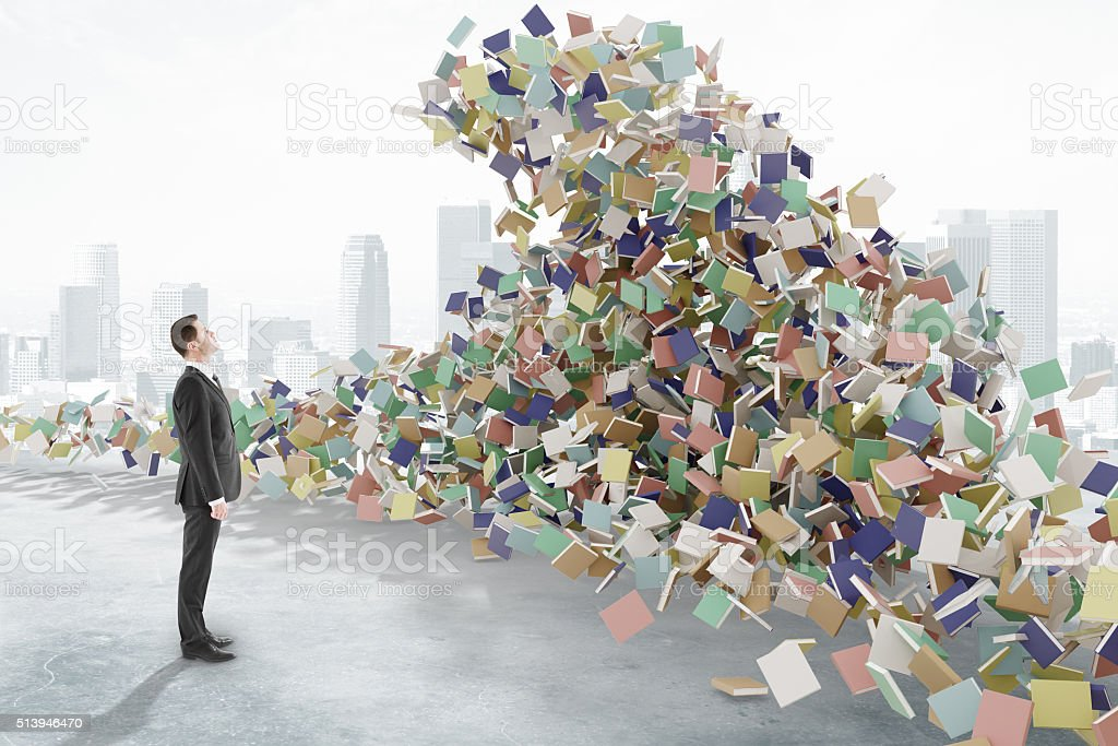 Man looks at the tsunami waves consisting of books stock photo