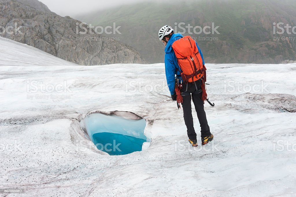Man looks curiously at glacial moulin stock photo