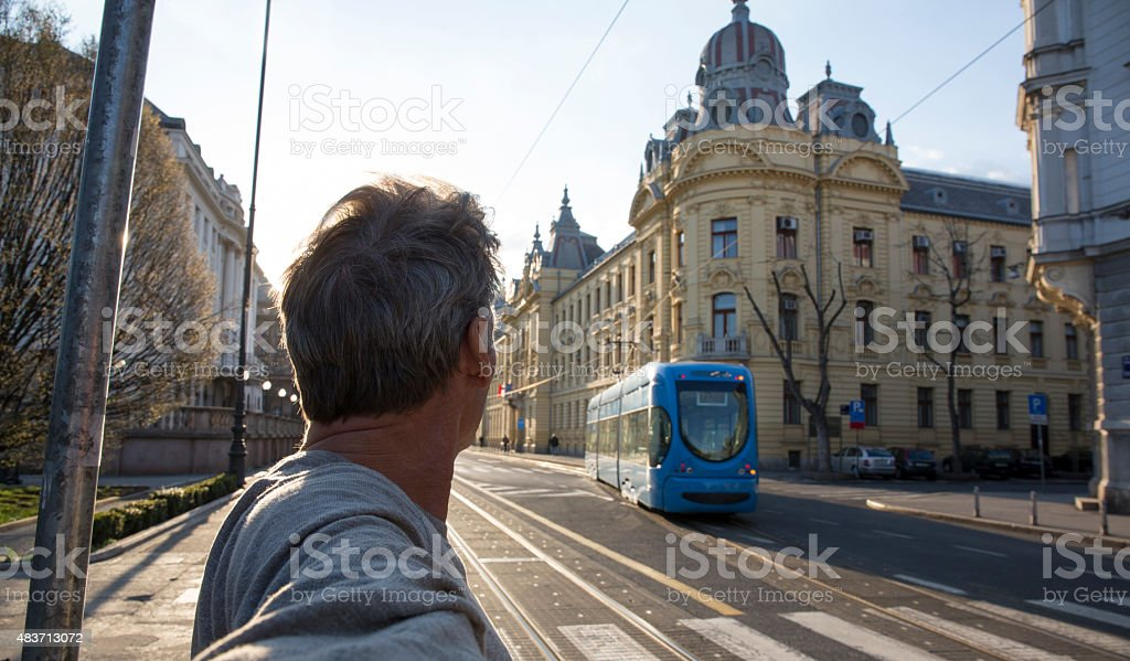 Man looks down urban road to approaching cablecar stock photo