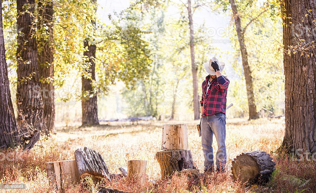 Man looks down while taking break from cutting firewood stock photo