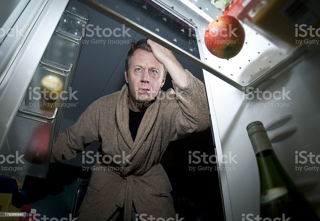 Man looks into the refrigerator for a snack stock photo