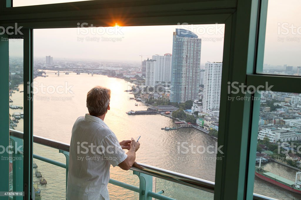 Man looks out from hotel railing, above city, river stock photo