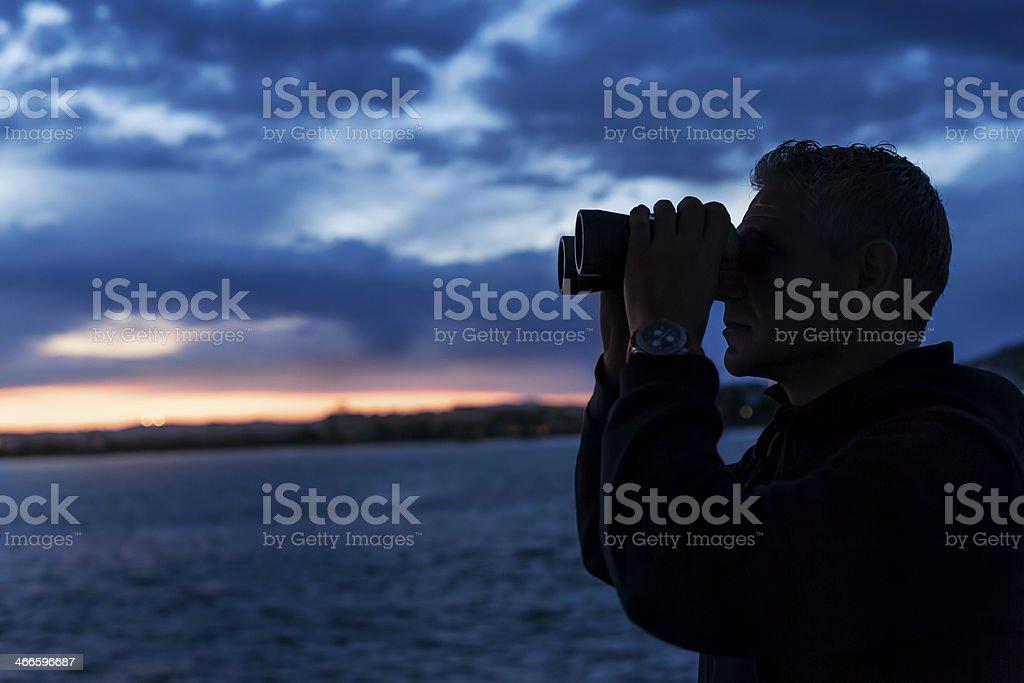Man looks through binoculars royalty-free stock photo