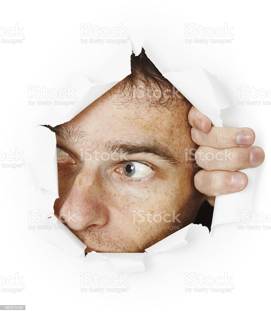 Man looks through hole stock photo