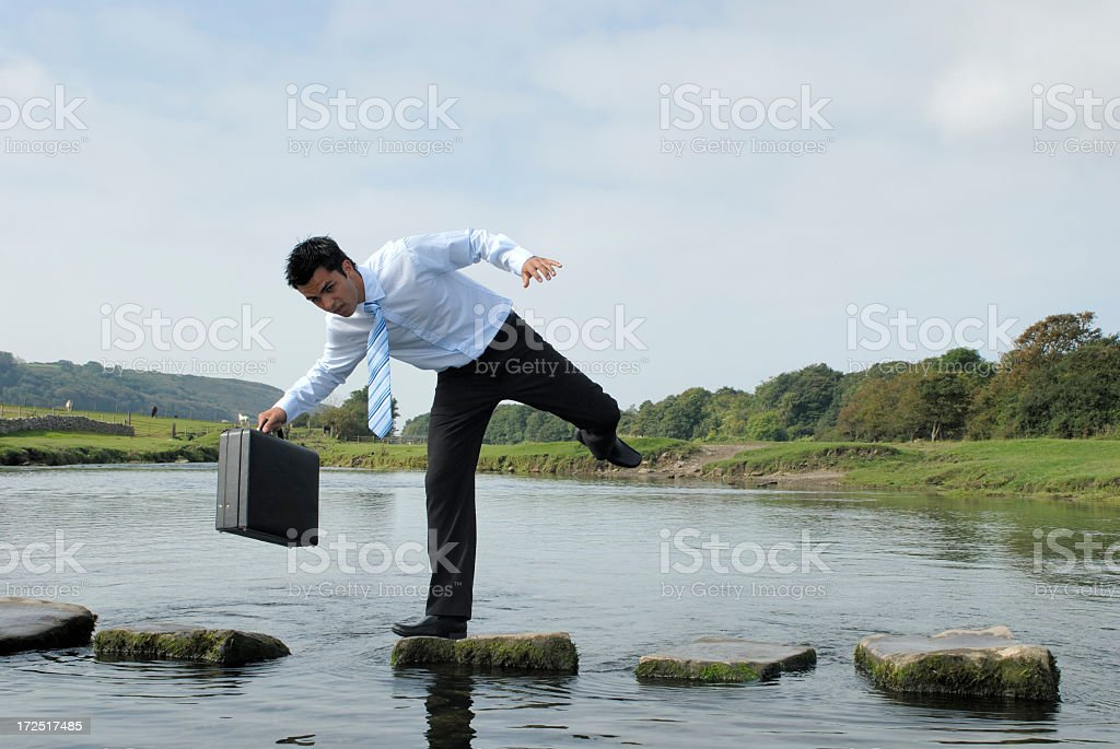 Man losing his balance on a rock near a pond  royalty-free stock photo