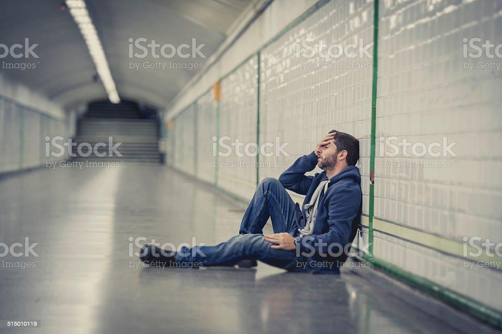 man lost in depression sitting on ground street subway tunnel stock photo
