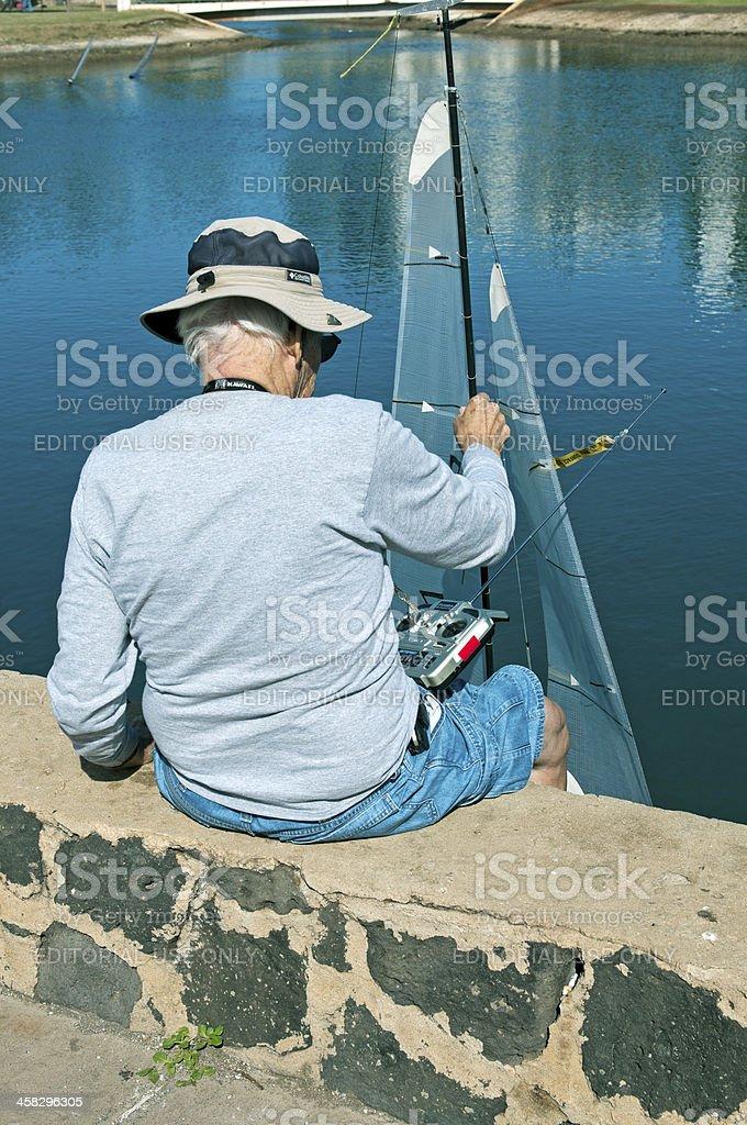 Man lowering toy sailboat to water in Honolulu HI royalty-free stock photo