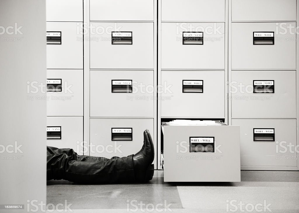 Man lying down beside filing cabinet royalty-free stock photo