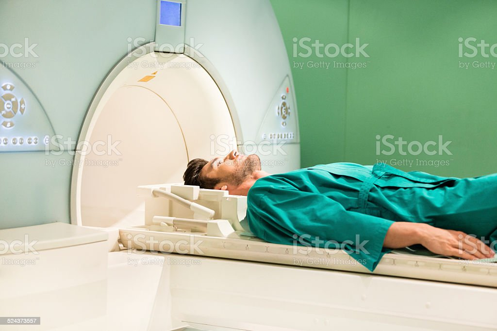 Young man lying down in CAT scan machine, waiting for MRI scan.