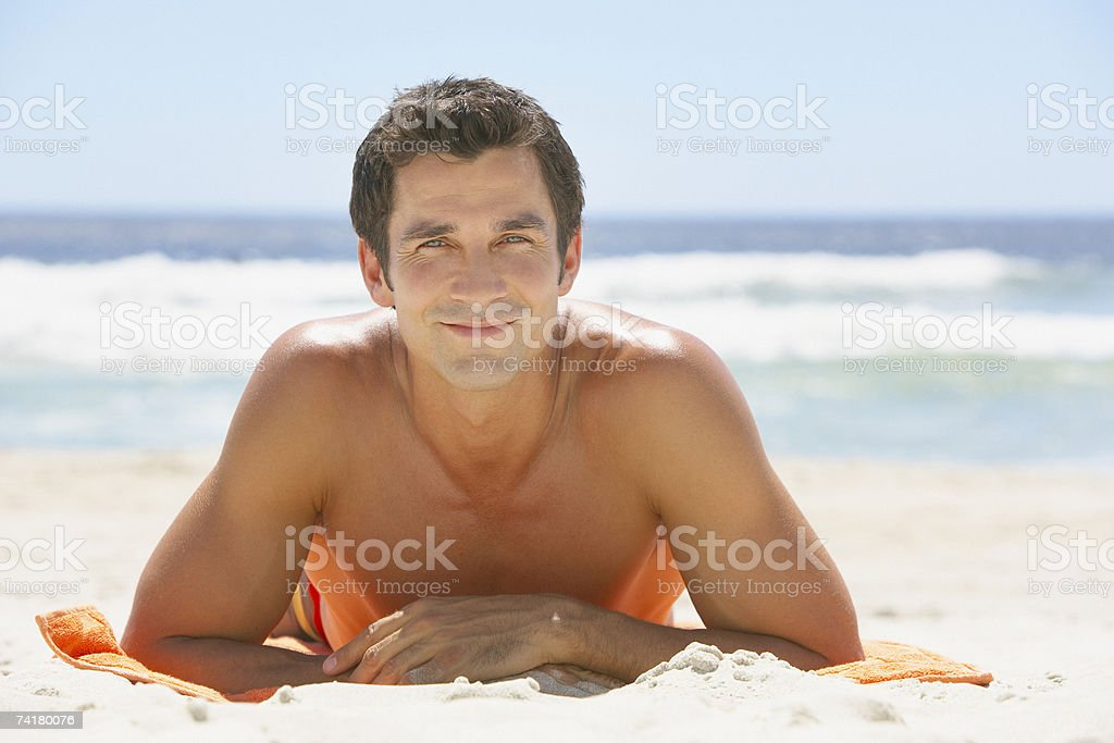 Man lying down on beach towel in sand royalty-free stock photo