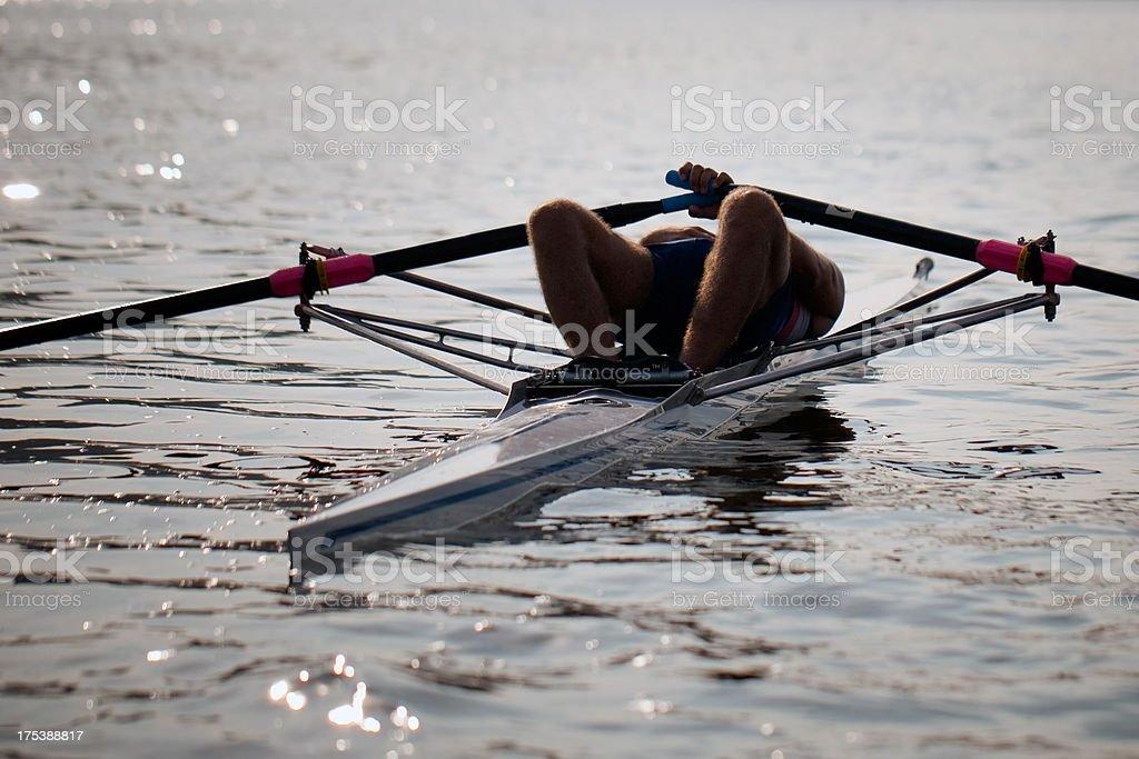 Man lying down on single scrull boat stock photo