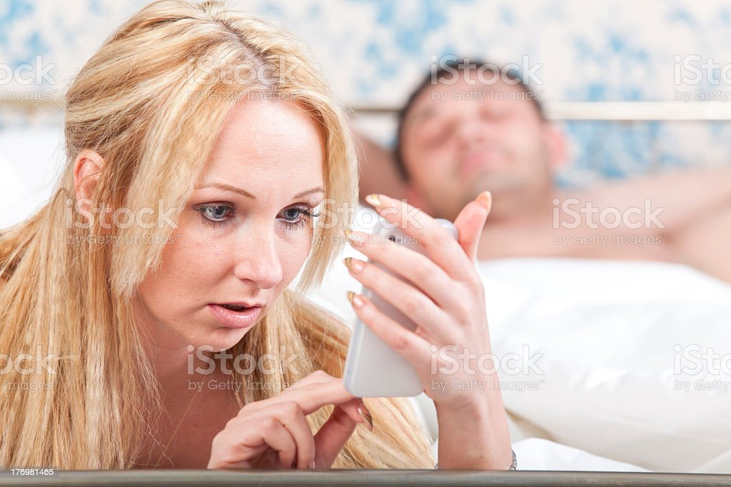 Man lying in bed while woman obsesses over her smartphone stock photo