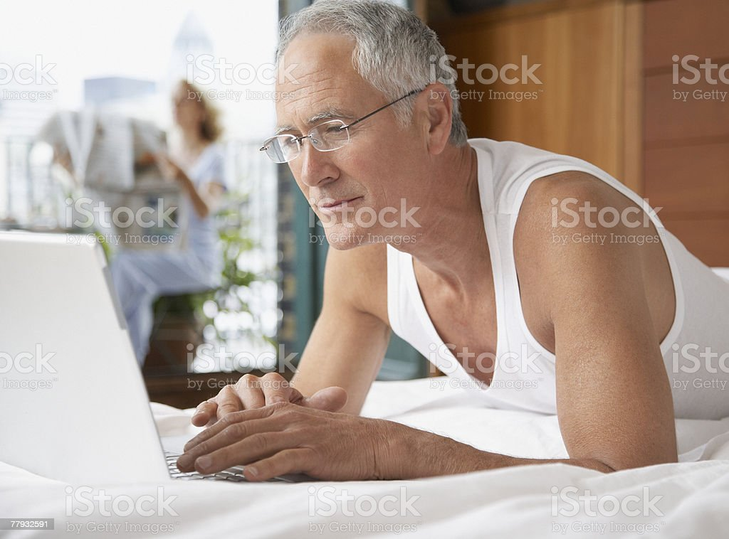 Man lying in bed with laptop and woman in background on balcony royalty-free stock photo