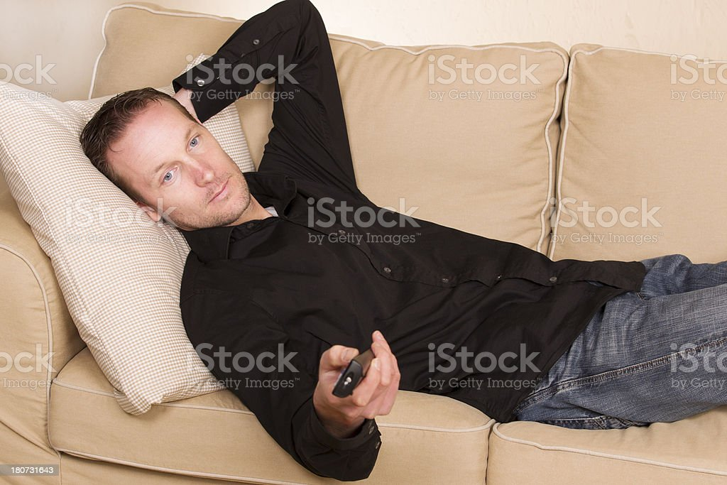 Man lying lazily on the couch stock photo