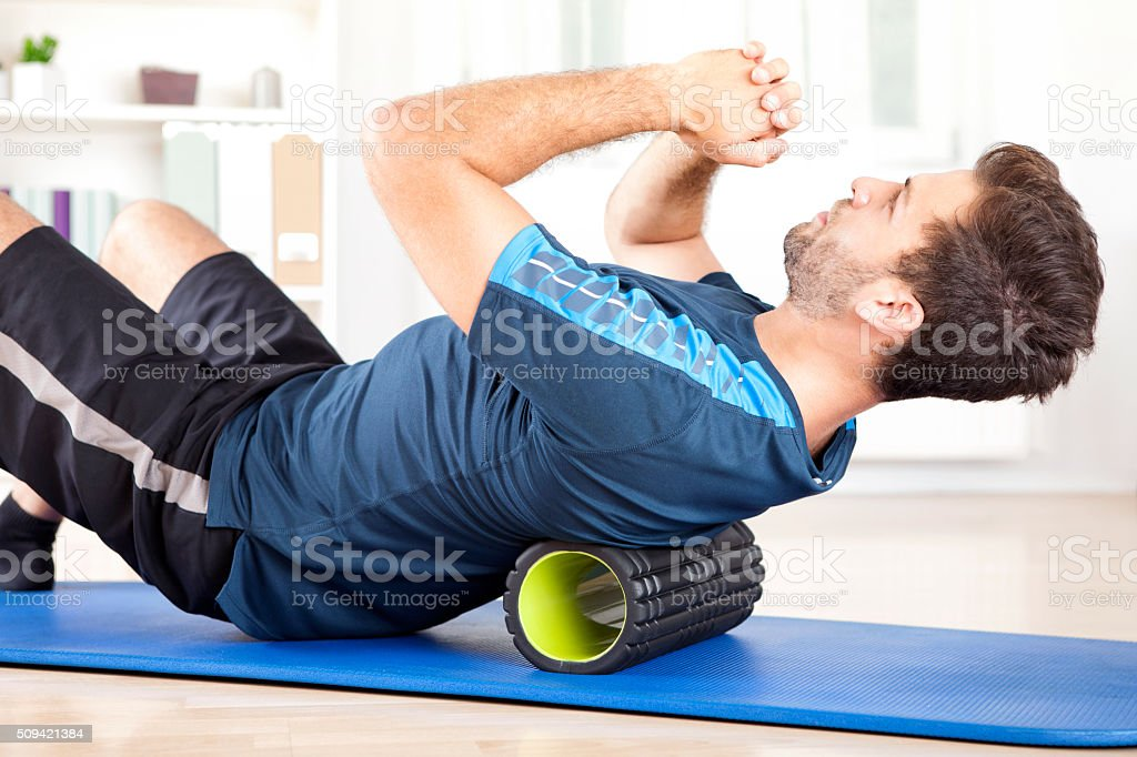 Man Lying on a Foam Roller While Doing an Exercise stock photo