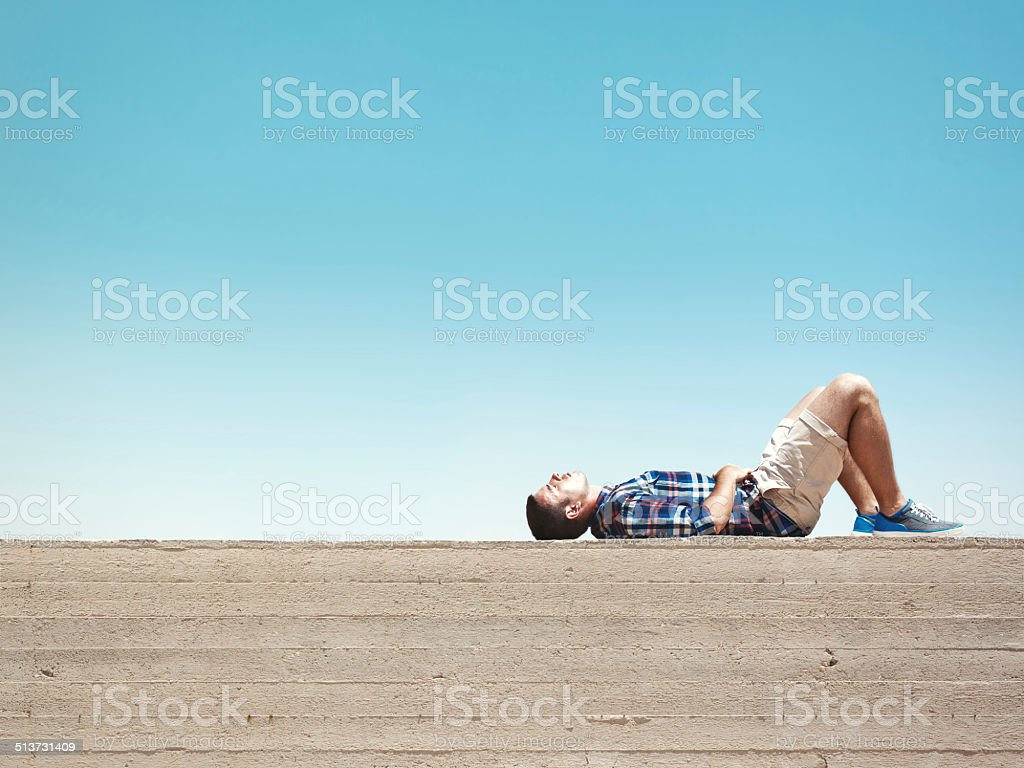 Man lying on cement wall stock photo