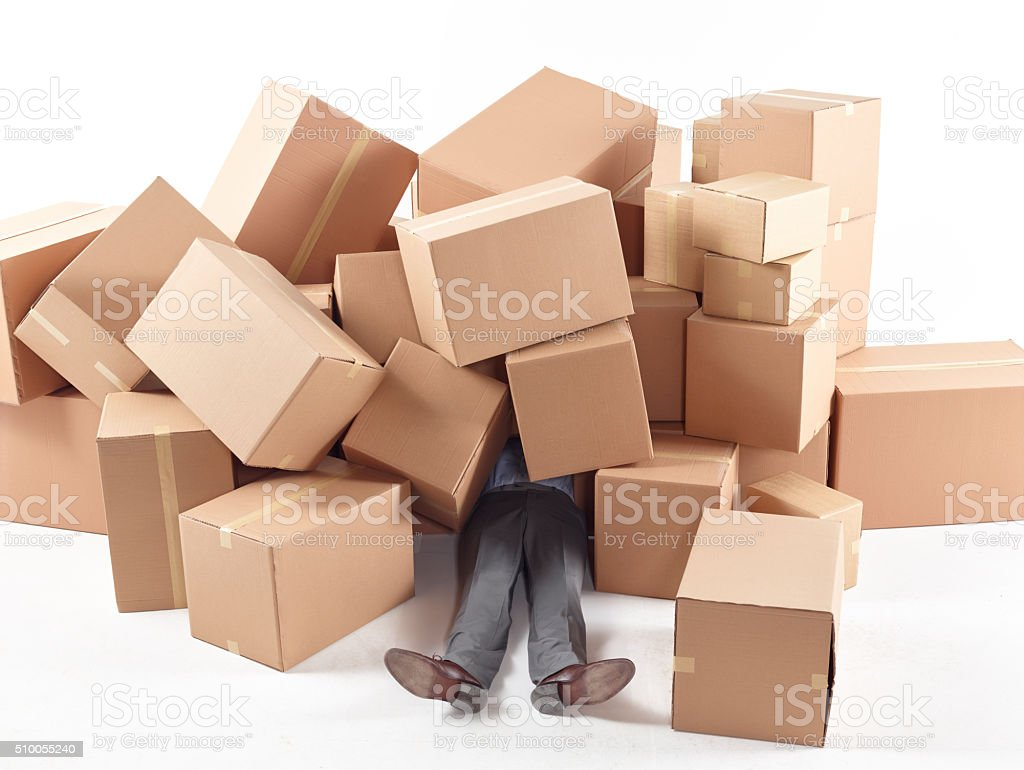 Man lying on floor covered by cardboard boxes stock photo