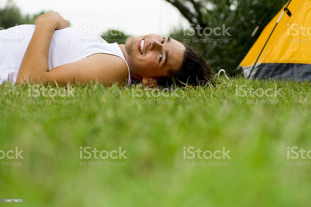 Man lying on grass near tent royalty-free stock photo