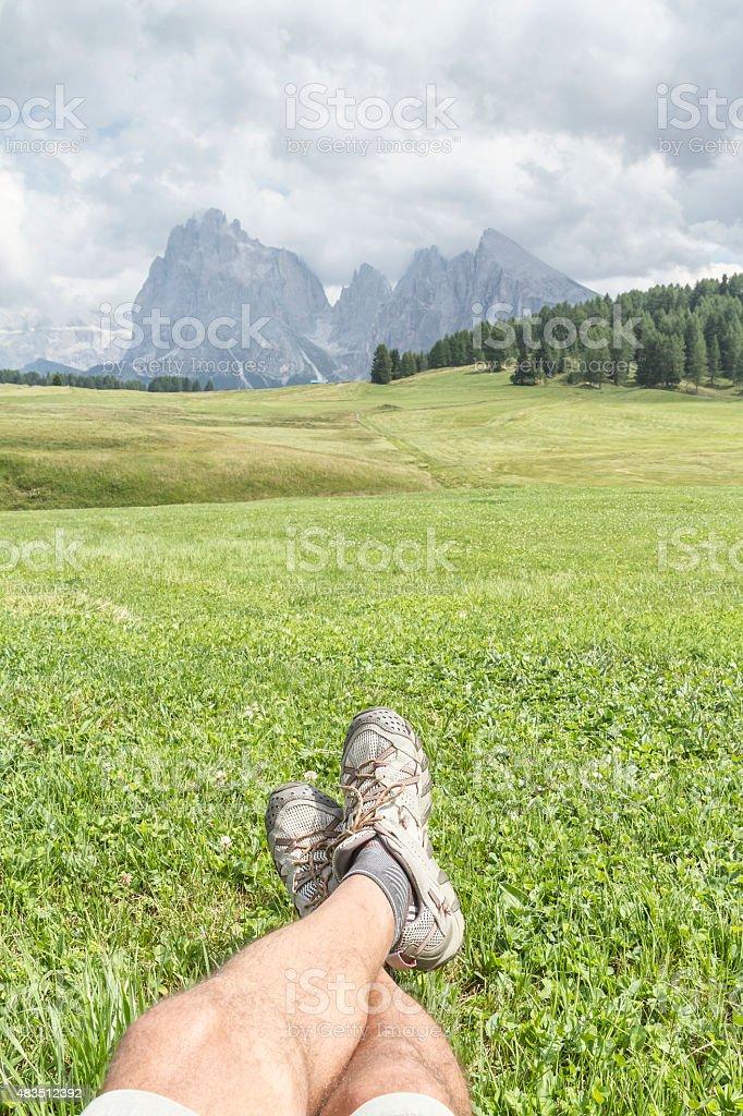 Man lying on grass watching Langkofel and Plattkofel stock photo