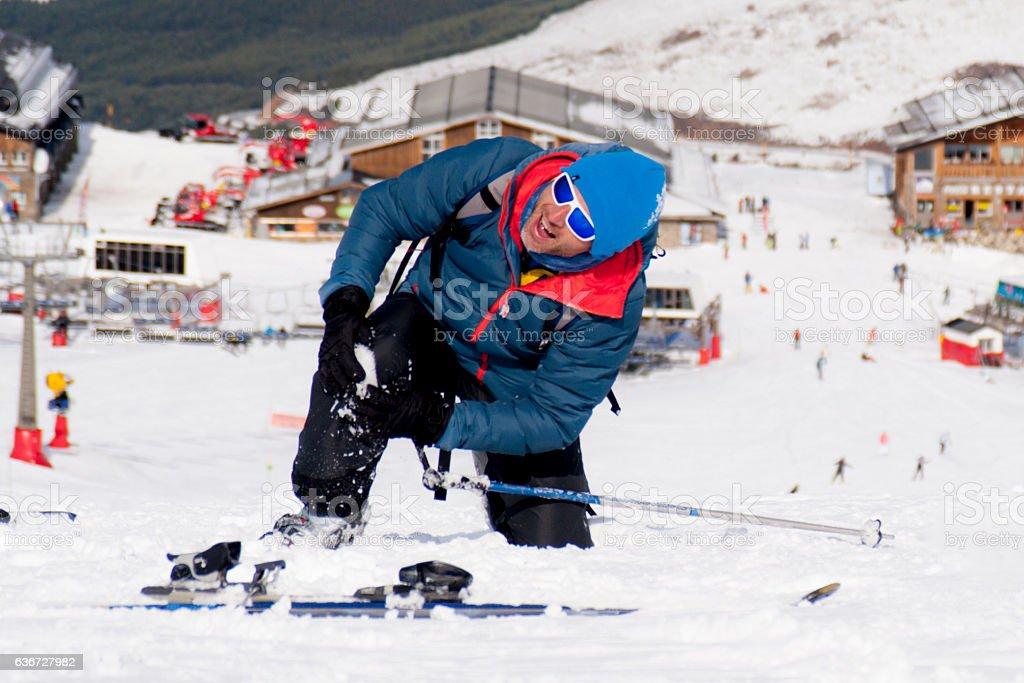 man lying on snow ski crash injured knee in pain stock photo