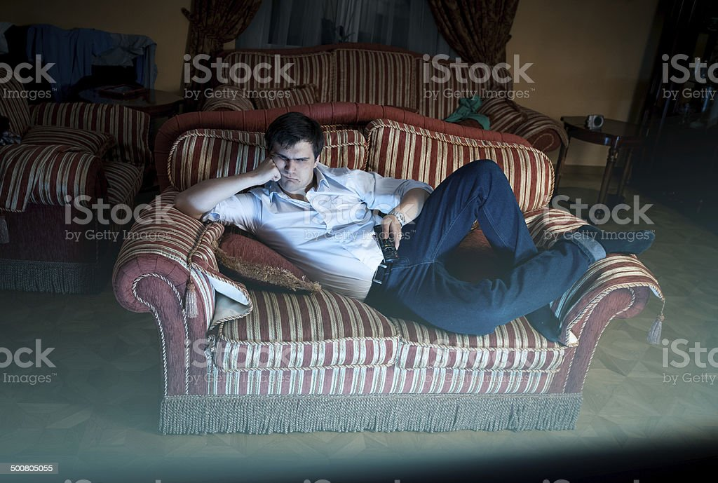 man lying on sofa and watching TV at night stock photo