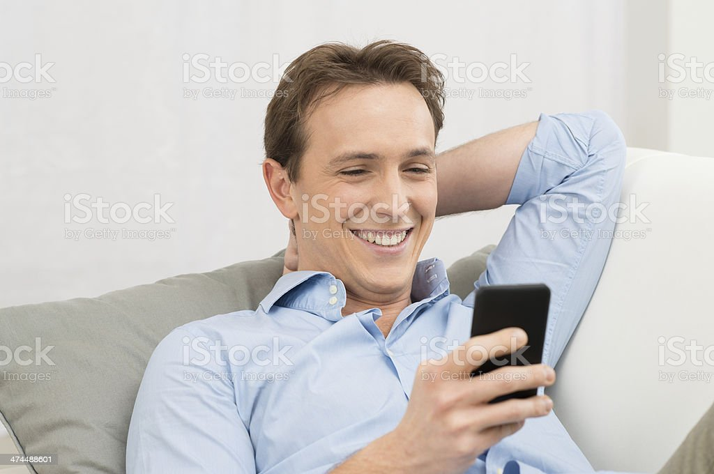 Man Lying On Sofa With Cellphone royalty-free stock photo