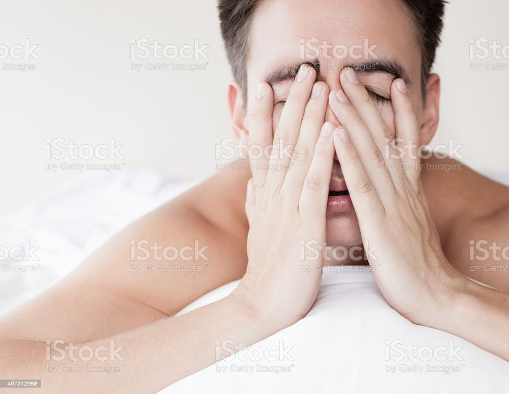 Man lying on stomach with his fingers covering his eyes stock photo