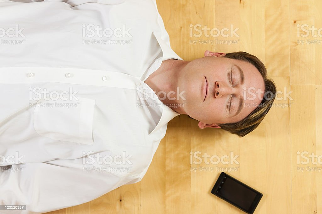 Man lying on the floor beside mobile phone royalty-free stock photo