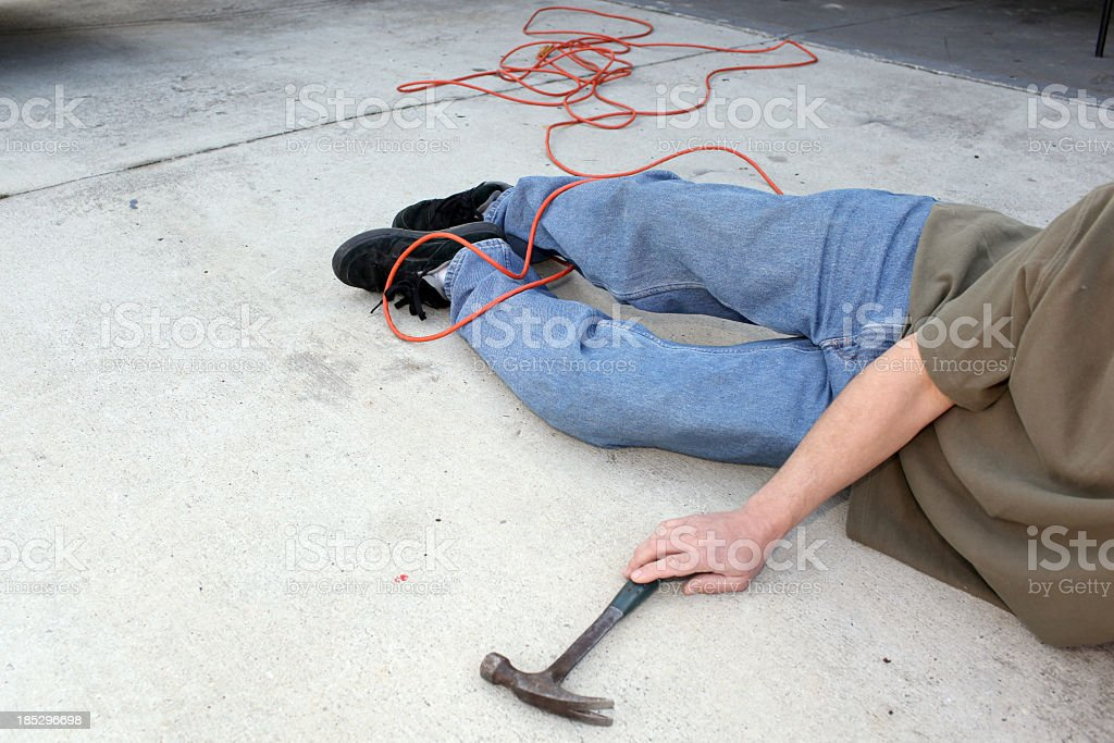 Man lying on the floor with a hammer in his hand stock photo