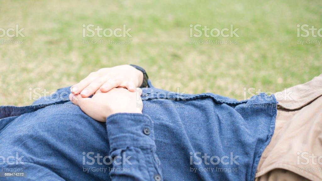 Man lying on the green field stock photo