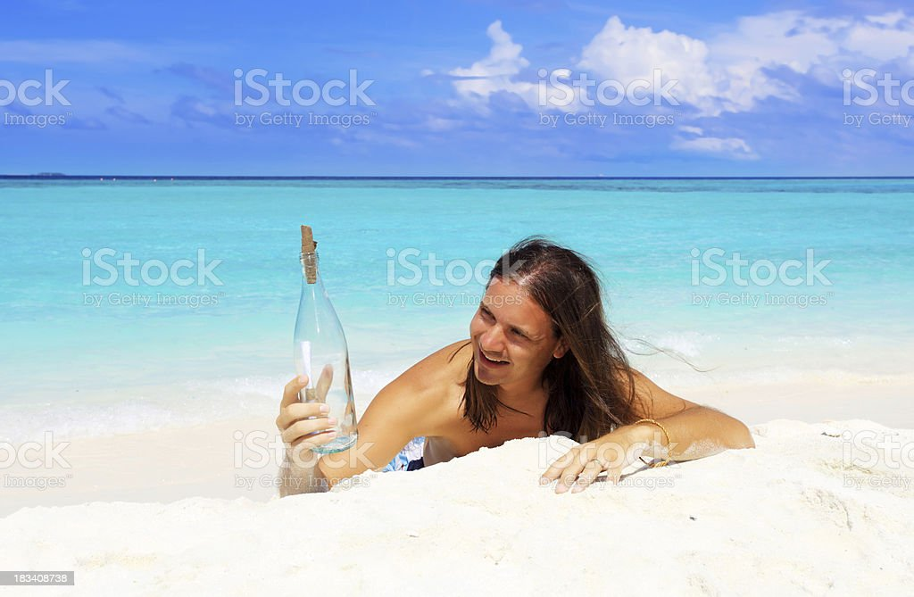Man lying on the sand and holding bottle with message. royalty-free stock photo