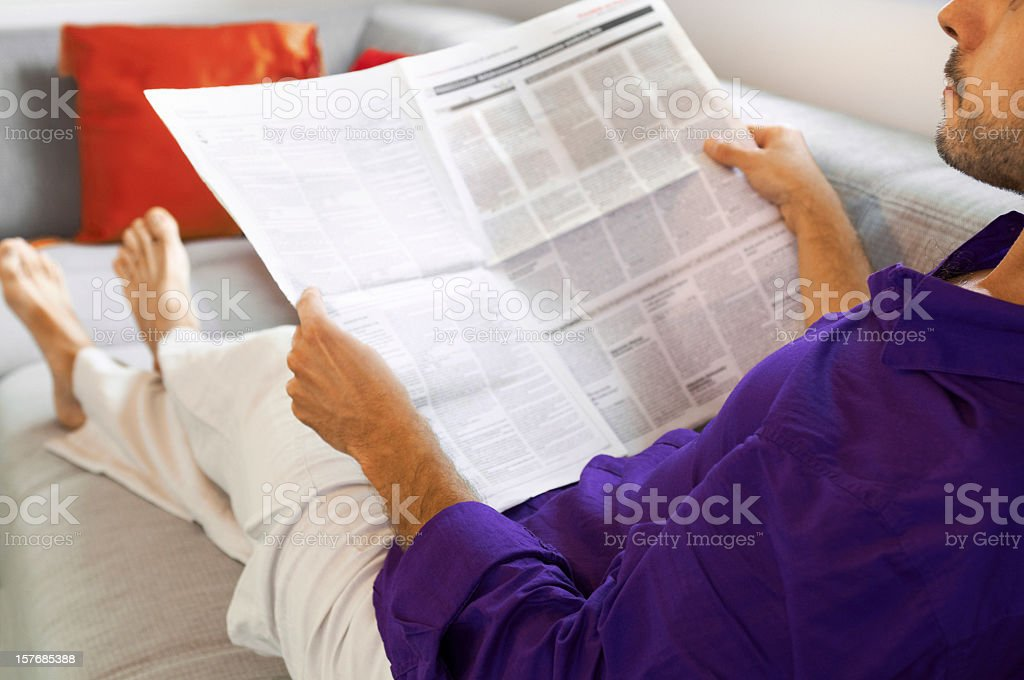 Man lying on the sofa with newspaper, relaxing after work royalty-free stock photo