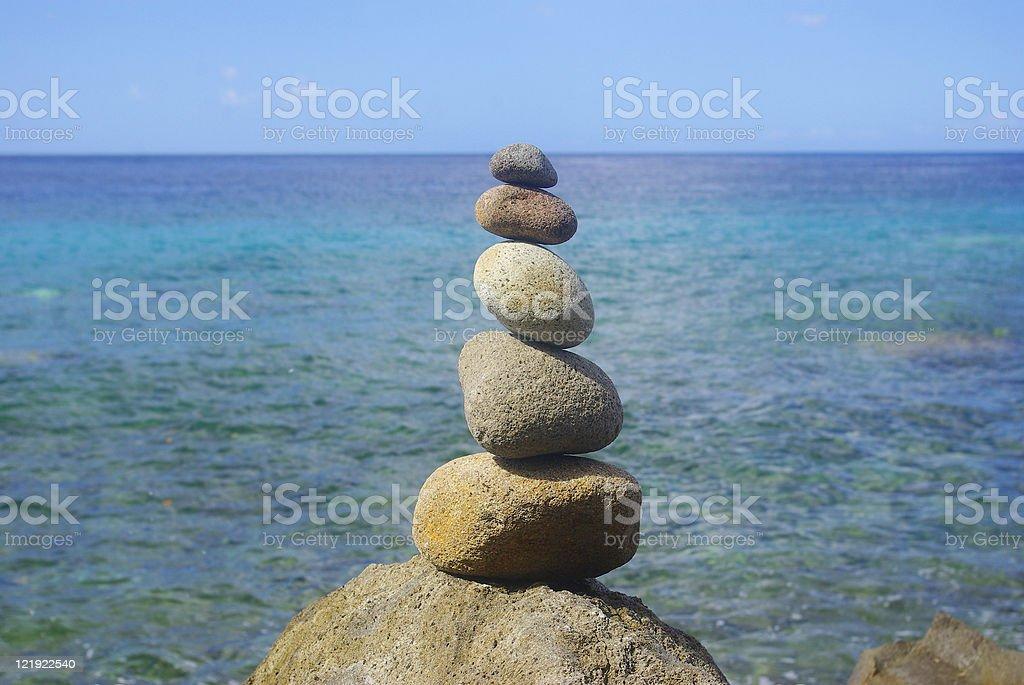 man made stack of rocks near sea stock photo