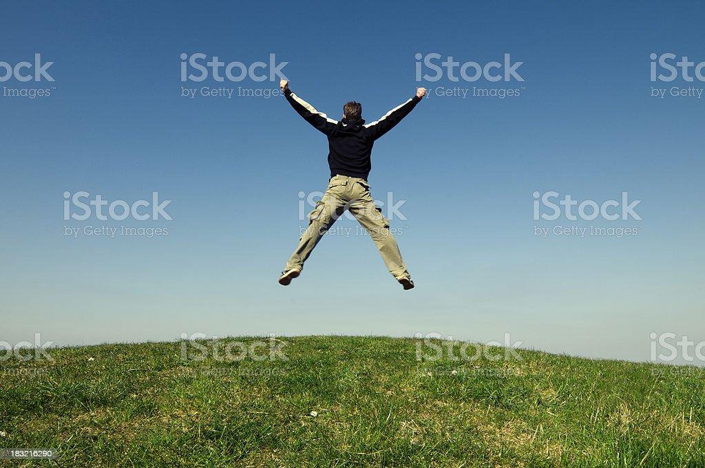 Man makes a big jump on hill stock photo