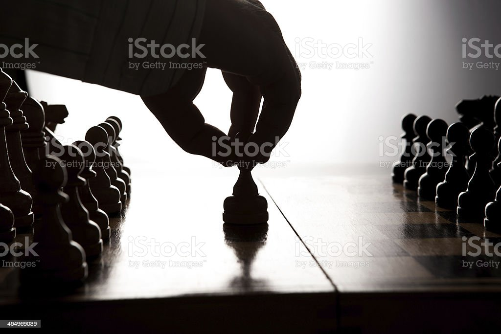 man makes a move chess figure stock photo
