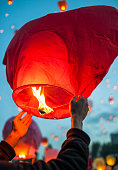 Man makes a wish and launches red paper lantern