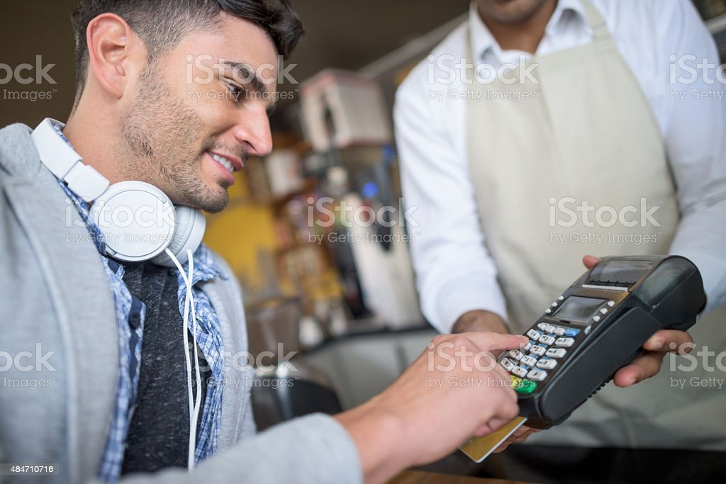 Man making a credit card payment at a cafe stock photo