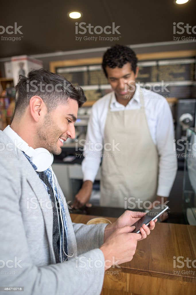 Man making a smart payment at a cafe stock photo
